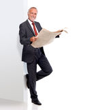 Mature business man with newspaper, leaning against a wall. Wearing a suit Royalty Free Stock Photo