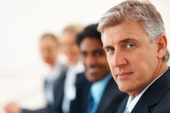 Mature business man with other staff at the back Stock Images