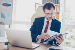 Mature business man is reading his notes, preparing for the meet. Ing. He is broker, wearing suit and red tie, glasses, sitting in the modern office stock image