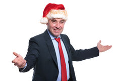 Mature business man in santa claus hat is welcoming Stock Images