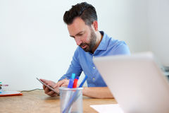Mature business man sitting at his desk using digital tablet. Portrait of mature business man sitting at his desk using digital tablet royalty free stock photos