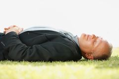Mature business man sleeping on grass Stock Photos