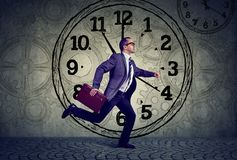 Mature business man in suit running on time stock photo