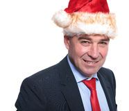 Mature business man wearing a christmas hat and smiles. Face of a happy mature business man wearing a christmas hat and smiles to the camera Royalty Free Stock Image
