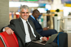 Mature business traveler. Portrait of happy mature business traveler using laptop at airport Royalty Free Stock Images