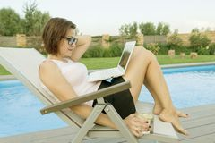 Mature business woman, freelancer, blogger with computer laptop and glass of water near the pool.  royalty free stock images