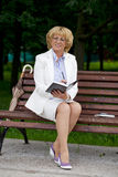 Mature business woman in a jacket with diary sitting on a bench Royalty Free Stock Images