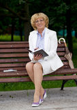 Mature business woman in a jacket with diary sitting on a bench Royalty Free Stock Photos