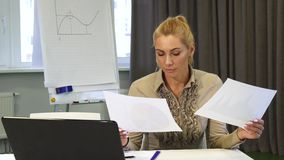 Mature business woman looking confused while examining documents. Beautiful mature business woman examining papers at the office looking confused and puzzled stock video