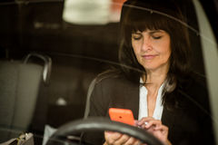 Mature business woman looking to phone in car Stock Images