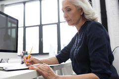 Mature business woman making notes on a piece of paper. Cropped image of a mature business woman making notes on a piece of paper at her desk Stock Images