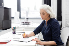 Mature business woman making notes on a piece of paper. At her desk Royalty Free Stock Photography
