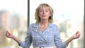 Mature business woman meditating indoor in office. stock video footage