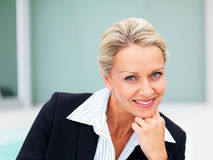 A mature business woman smiling with hand on chin Stock Image