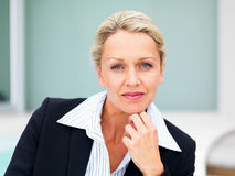 A mature business woman smiling with hand on chin Royalty Free Stock Photography