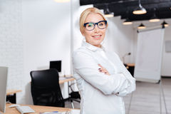 Mature business woman standing with arms folded in office Stock Image