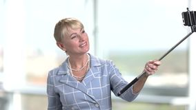 Mature business woman using selfie stick. stock video footage