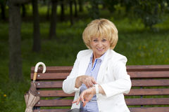 Mature business woman in a white jacket shows on his watch Royalty Free Stock Images