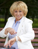 Mature business woman in a white jacket shows on his watch Stock Photo