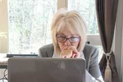 Mature business woman working on computer. Royalty Free Stock Photography