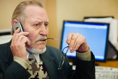 Mature businessman. Talking on the phone, checking out a document on his computer monitor Royalty Free Stock Images