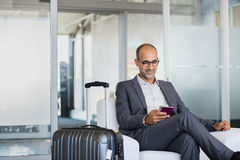 Mature businessman at airport. Mature businessman using mobile phone at the airport in the waiting room. Business man typing on smartphone in lounge area stock images