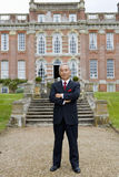 Mature businessman with arms crossed in front of manor house, portrait Stock Images