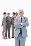 Mature businessman with arms folded and team behind him Stock Photos