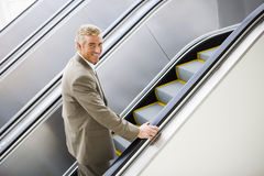 Mature businessman ascending escalator, smiling, side view, portrait Royalty Free Stock Photography