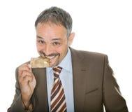 Mature businessman bites his credit card Stock Photography