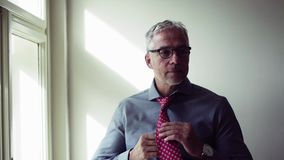 Mature businessman on a business trip standing in a hotel room, getting dressed. Mature businessman with glasses on a business trip standing in a hotel room stock footage