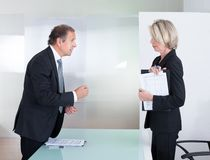 Mature businessman and businesswoman fighting Royalty Free Stock Photography