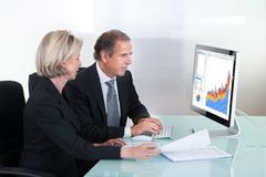 Mature businessman and businesswoman looking at graph Stock Photo