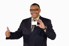 Mature businessman with card posing thumbs up. A smiling mature African-American businessman showing a business card with copy space and posing with the thumbs Royalty Free Stock Images