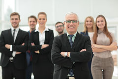 Mature businessman and cheerful business team on office backgrou Stock Images