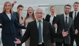 Mature businessman and cheerful business team on office backgrou. Successful and confident business team celebrating win Royalty Free Stock Photography