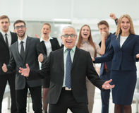 Mature businessman and cheerful business team on office backgrou. Successful and confident business team celebrating win Royalty Free Stock Photos