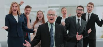 Successful and confident business team celebrating win. Mature businessman and cheerful business team on office background Stock Photo