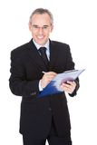 Mature businessman with clipboard Stock Photography