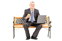 Mature businessman with coffee cup working on a laptop and sitti Royalty Free Stock Photo
