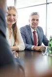 Mature businessman with colleagues at conference table in office Royalty Free Stock Images