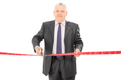 Mature businessman cutting a red tape Royalty Free Stock Photos