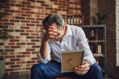 Mature businessman in deep desperation. I lost everything.Tired depressed middle aged man is sitting on chair. He holding frame and glass of whiskey Stock Image