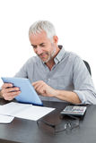 Mature businessman with digital tablet and calculator at desk Stock Image