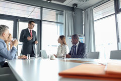 Mature businessman discussing with colleagues in meeting room Royalty Free Stock Photos