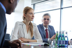 Mature businessman discussing with colleagues at table in board room Royalty Free Stock Images