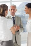 Mature businessman discussing with female colleagues Stock Image