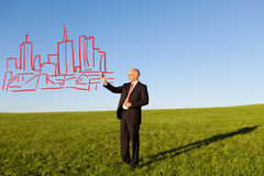 Mature Businessman Drawing Buildings In Field Stock Photo
