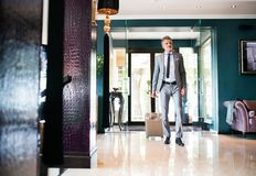 Mature businessman entering hotel with luggage. Royalty Free Stock Photo