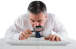 Mature businessman examining with magnifying glass Stock Photo